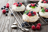 Meringues Pavlova cakes with fresh raspberry and blueberry on dark rustic wooden background, selective focus