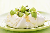 Pavlova cake with kiwi on green plate, closeup view