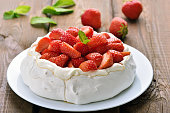 Pavlova cake with strawberry on wooden table