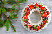 delicious pavlova cake wreath of french meringue and whipped cream, decorated with strawberry, figs, pomegranate and mint on old table with Christmas fir branch nearby, view from above