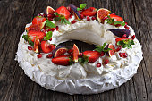 pavlova cake wreath - tender and elegant sweet dessert from french meringue and whipped cream, decorated with strawberry, figs, pomegranate and mint on napkin on dark table, view from above, close-up