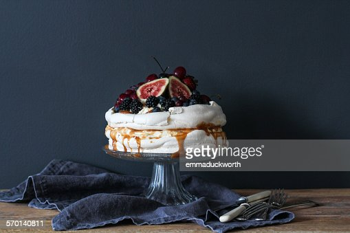 Pavlova decorated with berries on a cake stand