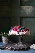 Vintage cake stand with Meringue dessert Pavlova with fresh blackberries and raspberries. Over blue wooden table with old tableware, textile napkin and snowdrops flowers. Dark rustic style.
