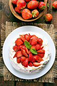 Pavlova meringue cake decorated with fresh strawberry, top view