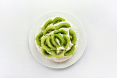 Pavlova meringue cake with kiwi slices and whipped cream over white stone background. Top view, flat lay