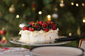 Delicious pavlova with cream, berries, passionfruit and mint. A staple of Australian Christmas lunch. Here it is in front if the Christmas tree where you can see defocussed Christmas lights and bauble