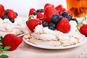 Pavlova is a meringue-based dessert with a crisp crust topped with strawberry and blueberry and whipped cream.