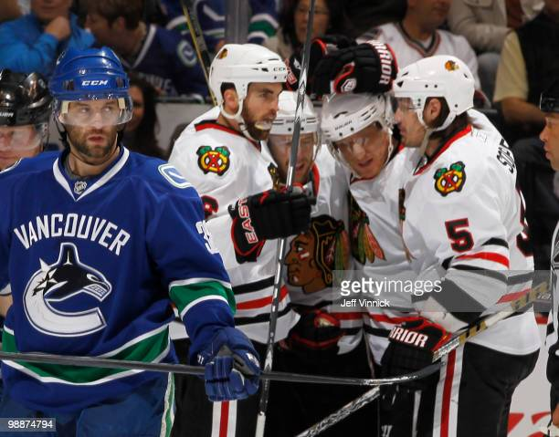 Pavol Demitra of the Vancouver Canucks skates away as Brent Sopel Marian Hossa Kris Versteeg and Andrew Ladd of the Chicago Blackhawks celebrate...