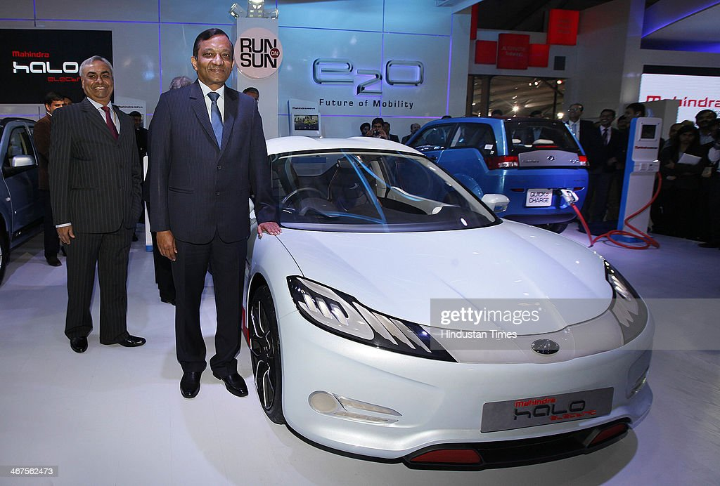 Pawan Goenka (C), President of Mahindra's automotive and farm equipment sectors, stands next to Mahindra's concept electric sports car 'Halo' after its unveiling during 12th Auto Expo, at India Expo Mart on February 6, 2014 in Greater Noida, India. Mahindra and Mahindra Ltd, India's largest utility vehicle maker, and South Korean company Ssangyong Motor Co Ltd will launch their first jointly developed engine in the first quarter of 2015, a senior executive of the Indian company said.