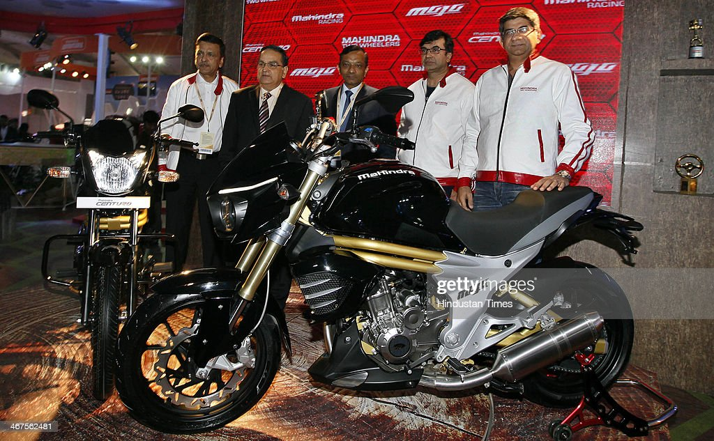 Pawan Goenka (C), President of Mahindra's automotive and farm equipment sectors, stands next to Mahindra's Mojo 300cc bike after its unveiling during 12th Auto Expo, at India Expo Mart on February 6, 2014 in Greater Noida, India. Mahindra and Mahindra Ltd, India's largest utility vehicle maker, and South Korean company Ssangyong Motor Co Ltd will launch their first jointly developed engine in the first quarter of 2015, a senior executive of the Indian company said.