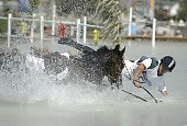 Pawel Spisak of Poland and horse Weriusz get wet when they fall into one of the obstacles in the team three day eventing cross country competition on...