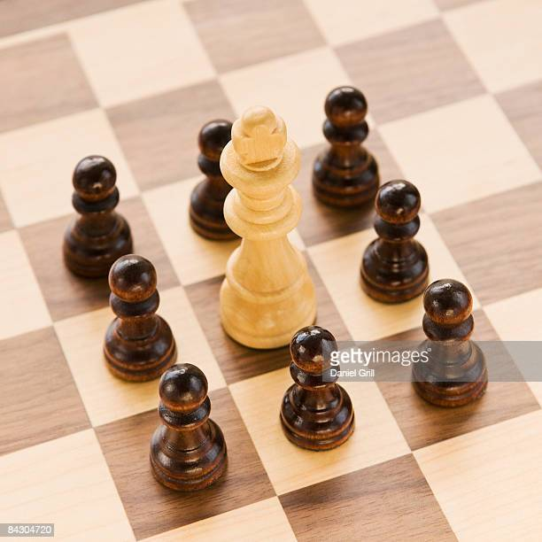 Pawns surrounding king on chessboard
