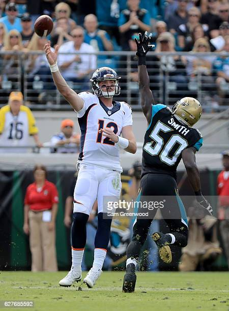 Paxton Lynch of the Denver Broncos attempts a pass as Telvin Smith of the Jacksonville Jaguars rushes at EverBank Field on December 4 2016 in...