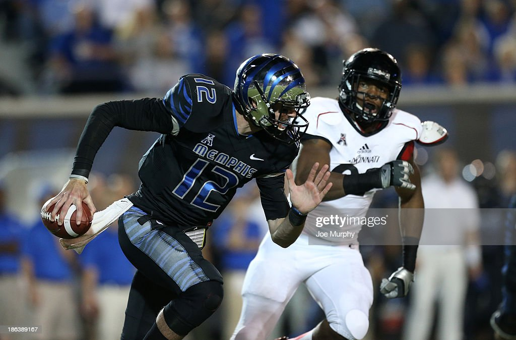 Paxton Lynch #12 of the Memphis Tigers scrambles against Silverberry Mouhon #$92 of the Cincinnati Bearcats on October 30, 2013 at Liberty Bowl Memorial Stadium in Memphis, Tennessee.