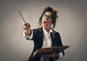 Teacher angrily shouting at someone while holding a stick and a book in her hands