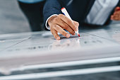 Closeup shot of an unrecognizable businessman writing notes on a whiteboard in an office