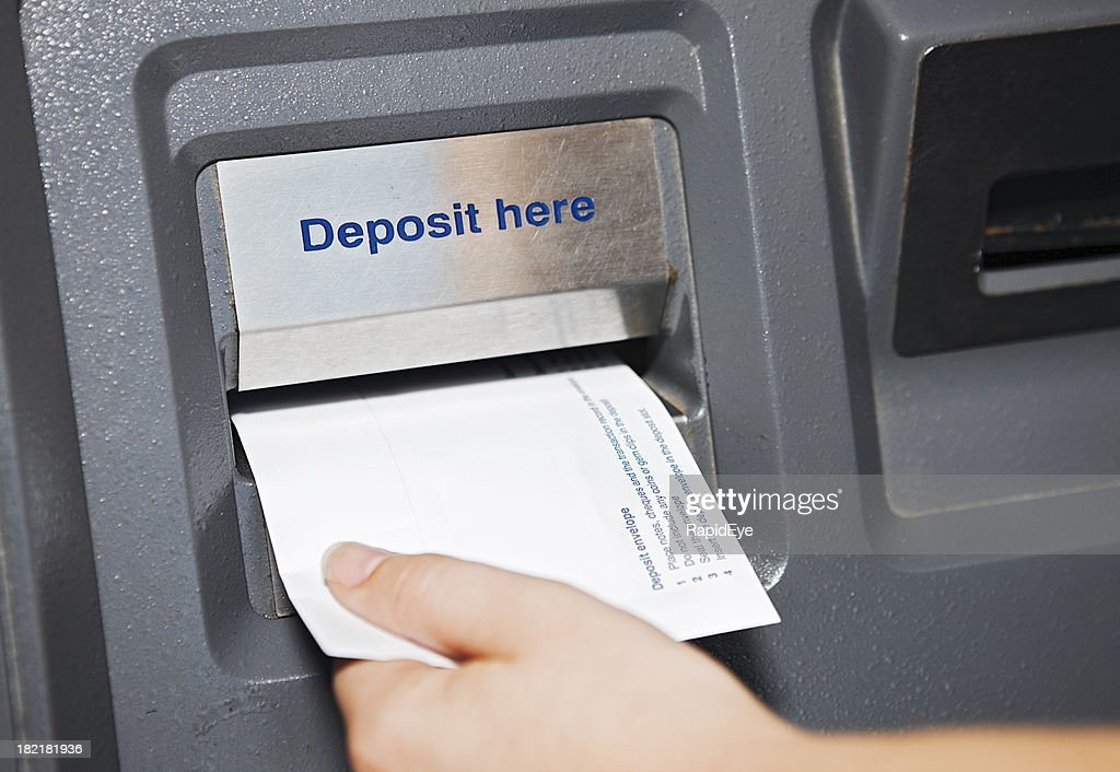 Pay day  - hand places deposit envelope in ATM slot
