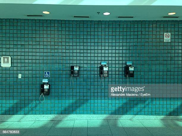 Pay Phones With Information Symbols On Wall