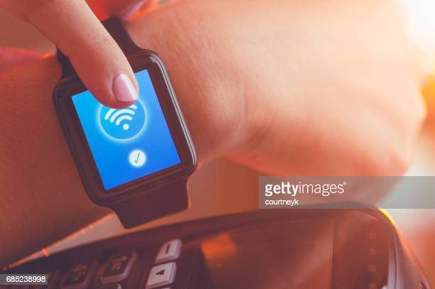 Paying with a smart watch.