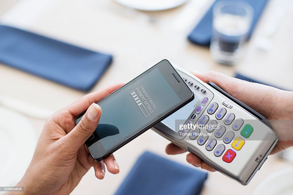 Paying with smartphone in restaurant : Stock Photo