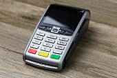 closeup on payment terminal isolated on wooden background