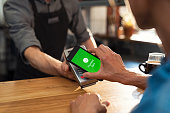Customer paying bill through smartphone using NFC technology. Closeup of hand making payment through contactless machine. Woman hand holding mobile phone with green screen and paying the bill with con