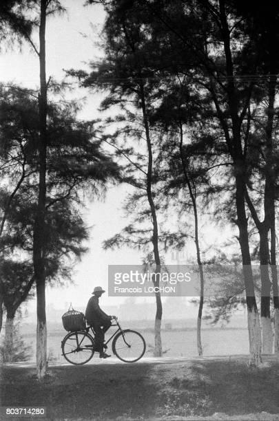 Paysan à vélo sur une route dans la commune de HingHoa en Chine en décembre 1977