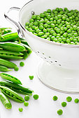 Pea pods by metal strainer filled with peas, close-up