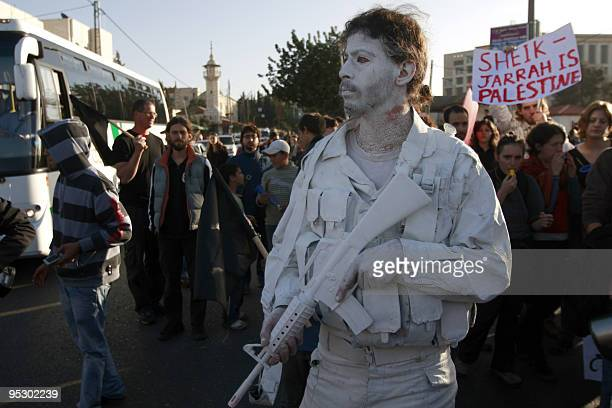 A peace activist dressed military clothes painted in white takes part in a protest near a disputed house in the neighborhood of Sheikh Jarrah in east...