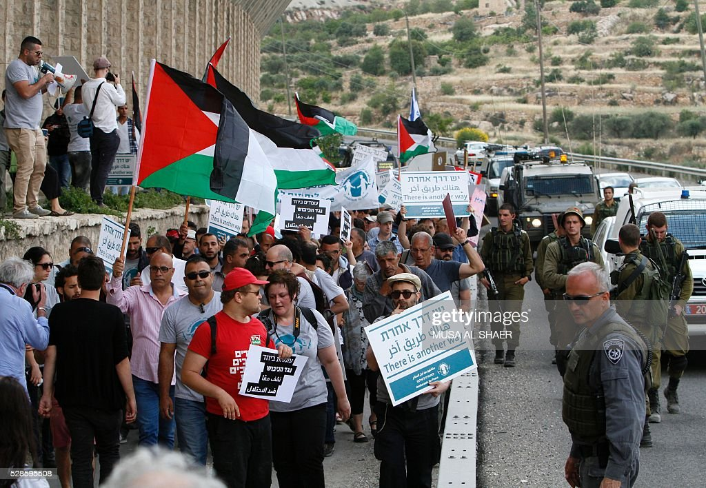 Peace activists hold placards during a joint Israeli-Palestinian peace march along the Israeli controversial separation wall in the West Bank city of Beit Jala between Bethlehem and Jerusalem, on May 6, 2016. / AFP / MUSA