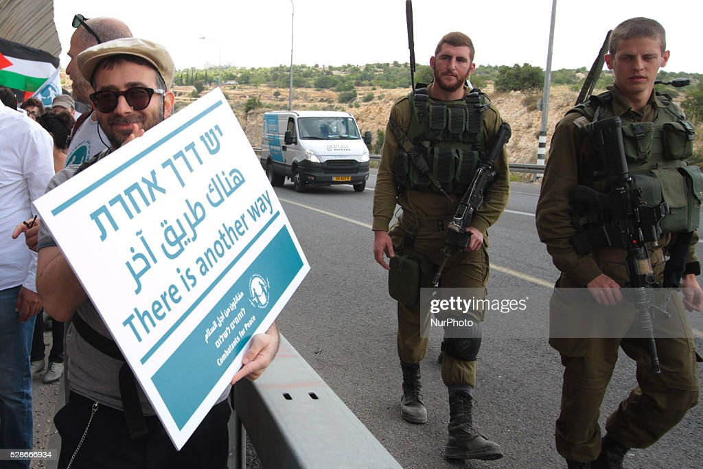 Peace activists hold placards during a joint Israeli-Palestinian peace march along the Israeli controversial separation wall in the West Bank city of Beit Jala between Bethlehem and Jerusalem, on May 6, 2016.