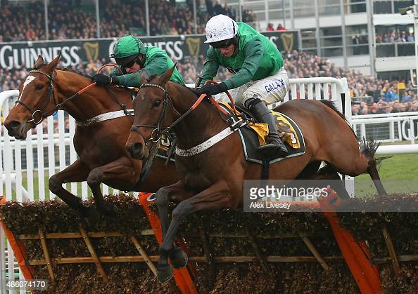 Peace And Co ridden by Barry Geraghty jumps the last fence alongside Top Notch ridden by Daryl Jacob on their way to victory in the JCB Triumph...