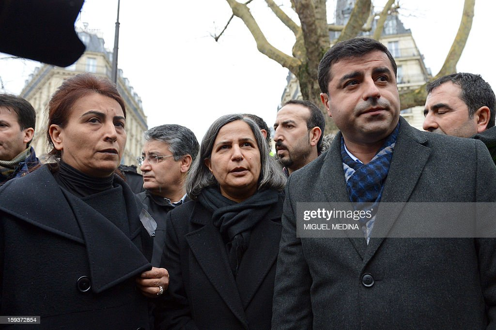 Peace and Democracy Party (BDP) chairman Selahattin Demirtas (R) and co-chairman Gultan Kisanak (C), and Democratic Society Congress (DTK) party member Aysel Tugluk (L) take part in a demonstration gathering hundreds of people of Kurdish origin on January 12, 2013 in Paris, two days after three Kurdish activits were found shot dead at Paris Kurdistan Information Bureau. Thousands of Kurds from all over Europe are gathered in Paris today for what is expected to be an angry protest over the killing of three female activists shot dead at least three times in the head, giving further credence to the theory of an execution-style hit. Kurdish activists have accused Turkey or rogue nationalist elements in the country's military of being behind the killings. AFP PHOTO / MIGUEL MEDINA