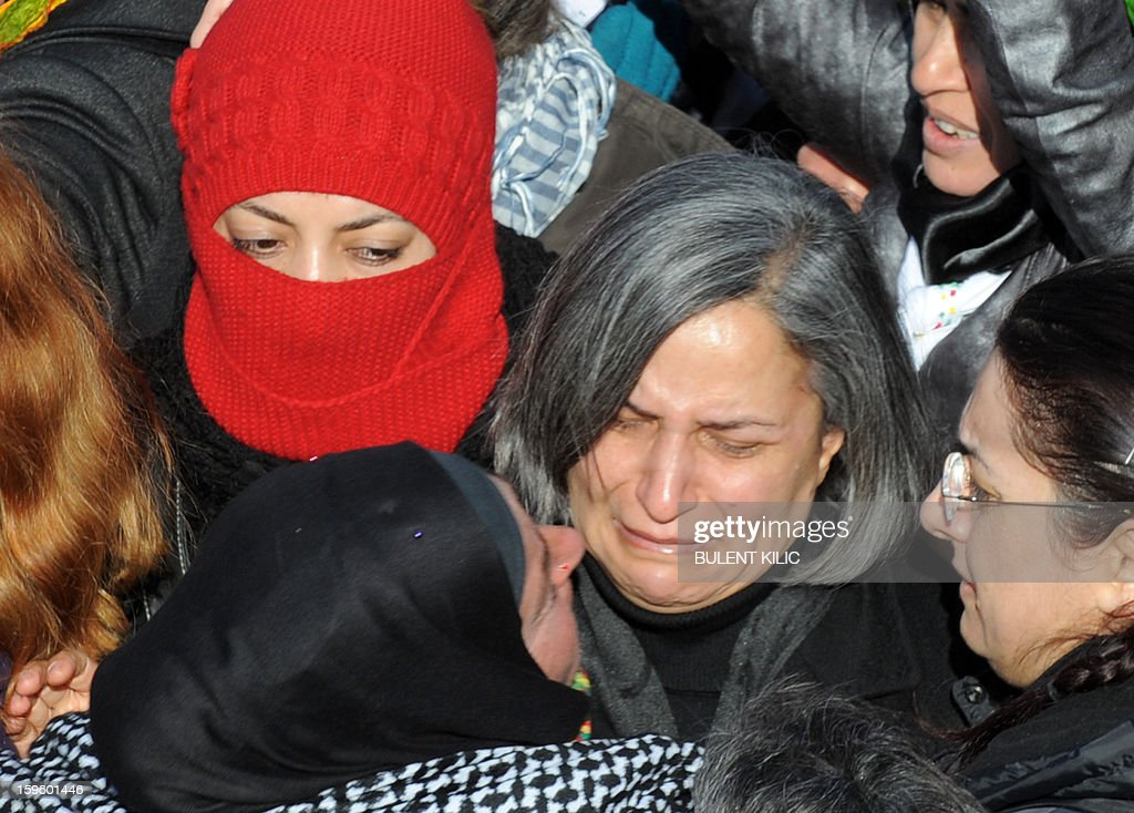 Peace and Democracy Party (BDP) Gulten Kisanak (C) cries upon the arrival of the coffins of the three top Kurdish activists, Sakine Cansiz, Fidan Dogan and Leyla Soylemez, shot dead in the French capital, on January 17 in Diyarbakir. Several thousand Kurds gathered Thursday in a square in Diyarbakir, the main city of Turkey's Kurd-majority southeast, to pay a final tribute to three Kurdish women activists who were assassinated in Paris last week. The growing crowd of participants, men and women adorned in white scarves, a symbol of peace, marched in a funeral many in Turkey feared would turn into a violent protest. The three women, one of them Sakine Cansiz, a co-founder of the outlawed Kurdistan Workers' Party (PKK), were found fatally shot, at least three times in their heads, at a Kurdish centre in Paris last week. French police were hunting the unknown assailants. AFP PHOTO/BULENT KILIC