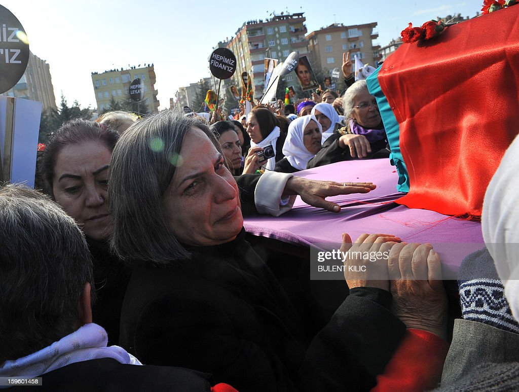 Peace and Democracy Party (BDP) Gulten Kisanak (C) touches the coffins of one the three top Kurdish activists, Sakine Cansiz, Fidan Dogan and Leyla Soylemez, shot dead in the French capital, on January 17 in Diyarbakir. Several thousand Kurds gathered Thursday in a square in Diyarbakir, the main city of Turkey's Kurd-majority southeast, to pay a final tribute to three Kurdish women activists who were assassinated in Paris last week. The growing crowd of participants, men and women adorned in white scarves, a symbol of peace, marched in a funeral many in Turkey feared would turn into a violent protest. The three women, one of them Sakine Cansiz, a co-founder of the outlawed Kurdistan Workers' Party (PKK), were found fatally shot, at least three times in their heads, at a Kurdish centre in Paris last week. French police were hunting the unknown assailants.
