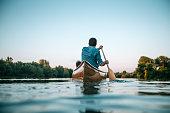Man paddling a canoe on a lake.