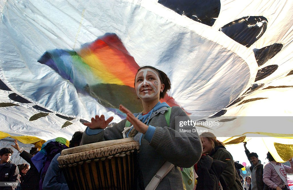 A peace demonstrator plays a drum while walking under a rainbow peace flag as she participates in an antiwar protest in Venezia Square February 15, 2003 in downtown Rome, Italy. Approximately one million peace protesters gathered to protest a possible U.S.-led war on Iraq.