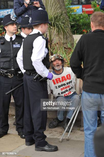 Peace protester Brian Haws sits handcuffed after being arrested after police officers entered the Democracy Camp based on Parliament Square hours...