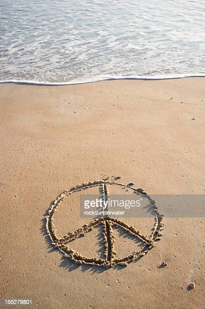 Peace symbol drawn in beach sand near ocean's edge