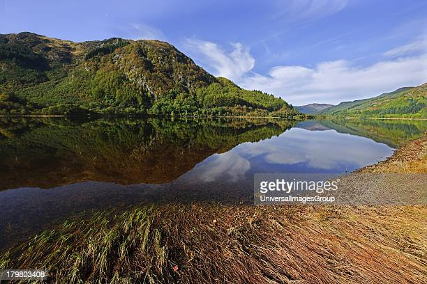 Peaceful Autumn reflections on water from the shore of Loch Lubneag Scotland United Kingdom