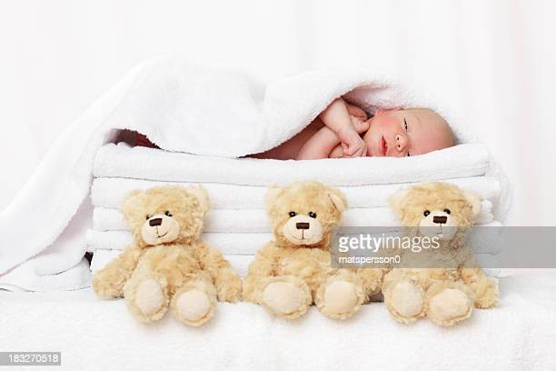 Peaceful baby lying on towels with teddy bears