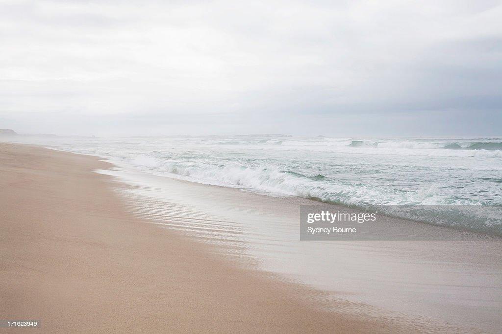 Peaceful beach scene with misty horizon : Stock Photo