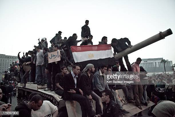 Peaceful demonstrators climb onto a Egyptian army tank in Tahrir Square on January 29 2011 in Cairo Egypt