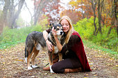 A happy, peaceful young woman has stopped walking her dog along a path in the autumn forest to hug him lovingly.