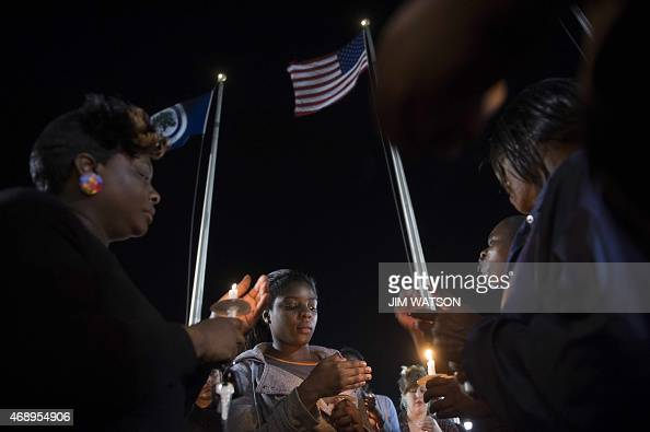 Peaceful protesters stand with candles as they gather outside the North Charleston City Hall in North Charleston SC April 8 after the latest in a...