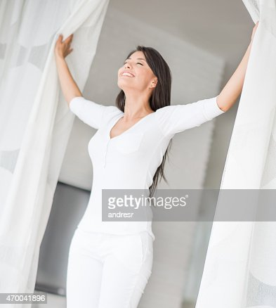 Peaceful woman at home opening the window