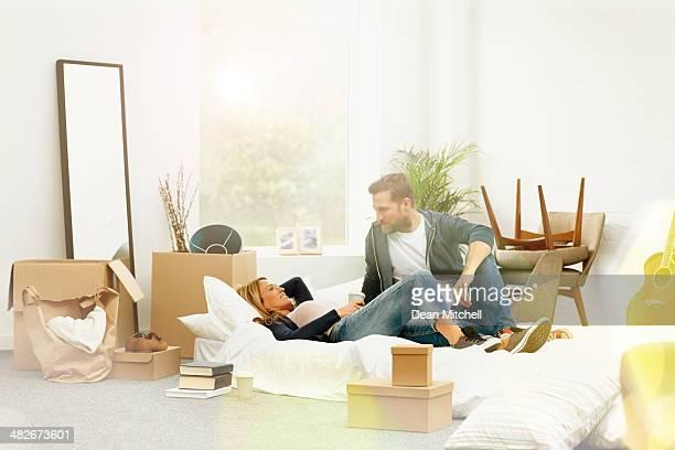 Calme jeune couple allongé parmi les boîtes défaits