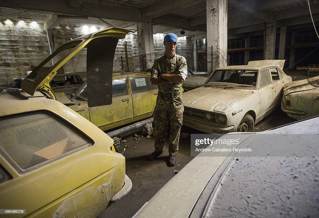 UN Peacekeeper, Guardsman, Christopher Walker, from the 1st Battalion Irish Guardsman looks on near imported cars from Japan, covered in dust and abandoned in the buffer zone in 1974, during a patrol of the buffer zone on June 12, 2014 in Nicosia, Cyprus. The buffer zone is patrolled by The United Nations Peacekeeping Force in Cyprus (UNFICYP), and originally set up by the Security Council in 1964 to prevent further fighting between the Greek Cypriot and Turkish Cypriot communities. After the hostilities of 1974 and in the absence of a political settlement to the Cyprus problem, UNFICYP has remained on the island to supervise ceasefire lines, and maintain a buffer zone,
