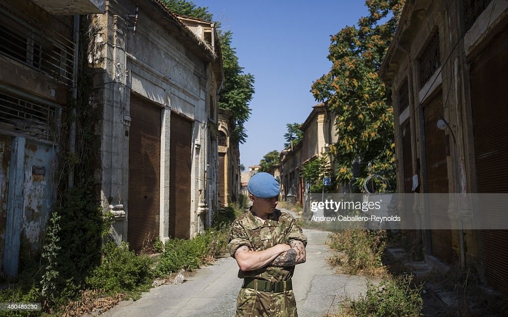 Peacekeeper Guardsman Garth McDowell from the 1st Battalion Irish Guardsman takes a brake during a patrol of the buffer zone on June 12 2014 in...