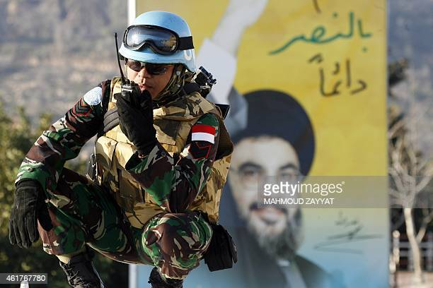 A peacekeeper of the United Nations Interim Force in Lebanon speaks on his talkiewalkie in front of a billboard bearing a portrait of Hezbollah chief...